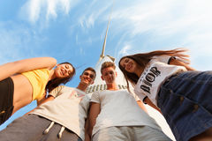 Group of teenagers. Young girls and boys hugging and smiling on a blue sky background. Friendship concept. Copy space. View from below of a group of teenage Royalty Free Stock Photos