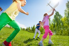 View from below of kids who run, hold airplane toy Royalty Free Stock Photos