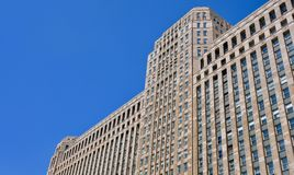 View of Merchandise Mart, Chicago from below. A view from below of Merchandise Mart in downtown Chicago, Illinois with a clear blue sky behind Stock Photo