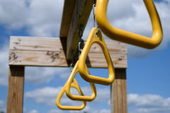 View From Below of Monkey Bar Rings Hanging From Wooden Beam. Monkey bar rings, hanging from wooden playground beam, viewed from below with blue sky and clouds Royalty Free Stock Images