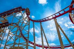 View from below of rollercoaster with people riding in orlando park in florida. People enjoying a ride in a high roller coaster in orlando florida royalty free stock photography