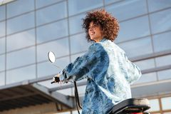 View from below of smiling curly woman sitting on motorbike Stock Photo