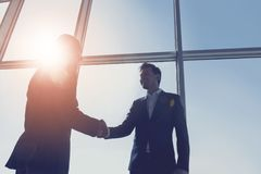 View from below of two young businessmen are standing in modern office with panoramic windows.  stock image