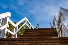 View From Below of White Wooden Staircase. View from below of a white wooden staircase outdoors, next to green ice plant Stock Photo