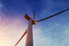 View from below of a wind turbine against beautiful cloudy sky and sun rays, electric generator with heaven on background Stock Images