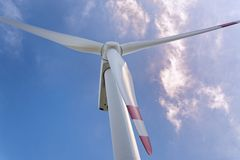 View from below on a wind turbine against dramatic cloudy sky. `Energy Hill` Georgswerder in Hamburg, Germany - public Information center about renewable forms royalty free stock images