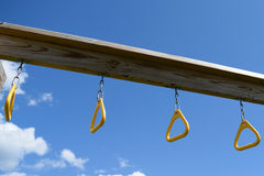 View From Below of Yellow Monkey Bar Rings Hanging From Wood Beam on Playground. Monkey bar rings, hanging from wooden playground beam, viewed from below with Stock Photos