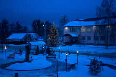 View of bench against christmas tree and shining lantern through snowing. Blue tone. Night shot. Stock Photo