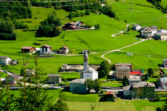 A View from Bernina Express. View from Bernina Express, Alpine village with a church in the middle surrounded by green grass meadows Royalty Free Stock Image