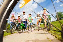 View from bicycle spoke on kids with helmets Stock Photo