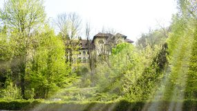 View of big abandoned hotel with old architecture hiddent in the forest in a sunny spring day stock photography