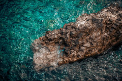 View of big cliff in wavy turquoise sea Royalty Free Stock Images