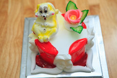 view of big light birthday cake with rabbit on wooden table Stock Images