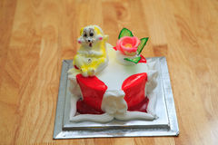 View of big light birthday cake with rabbit on wooden table. View of big light white red birthday cake with large rabbit and flower on wooden table against white Royalty Free Stock Photo