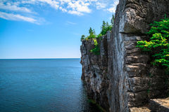 View of big long rocky cliff standing in Cyprus lake against blue bright sky at beautiful gorgeous Bruce Peninsula, Ontario. Great amazing majestic view of big Royalty Free Stock Photo