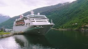 View of big white passenger ship on river at mountains covered by green woods. Nature. Landscape stock video footage