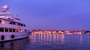 View of big white ship motor yacht at anchor in sea bay. View of motor yacht at anchor in sea bay with houses of old marine town after sunset in Mediterranean Royalty Free Stock Photos