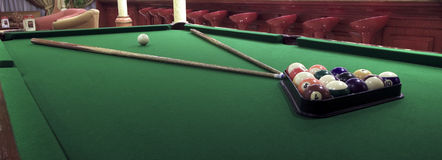 View of a billiard game before play. View of a billiard table from one of its corner showing seats of a bar at the back Royalty Free Stock Images