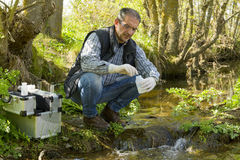 View of a Biologist take a sample in a river. Scientist and biologist hydro-biologist takes water samples for analysis Royalty Free Stock Photo
