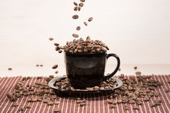 View of black cup standing on black plate with falling down roasted coffee beans on tablemat Stock Images