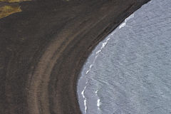 View of the black sand beach from above, Iceland. View of the black sand beach and blue water from above, Iceland royalty free stock image