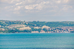 View of the Black Sea shore, green hills with houses, blue clouds sky. City Balchik coast, blue sea water Royalty Free Stock Images