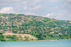 View of the Black Sea shore, green hills with houses, blue clouds sky. City Balchik coast, blue sea water Royalty Free Stock Photos