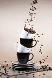 View of black and white cups on the stack of the plates with falling down brown roasted coffee beans on newspaper. View of black and white cups on the stack of royalty free stock photography
