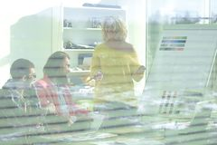 View through the blinds. a group of fashion designers in a modern Studio.  royalty free stock photography