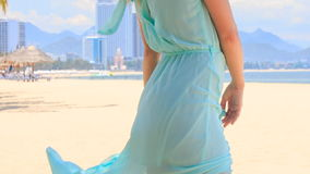 View of blonde girl in azure from down up to head under wind. Panorama of european slim blonde girl barefoot in light transparent frock from legs up to under stock footage