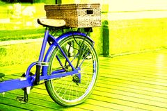 View of a blue bicycle with a basket on a bright yellow background royalty free stock photography