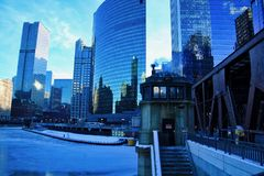 View of a blue and frigid winter morning in Chicago with a frozen river alongside an elevated bridge and bridgehouse. View of a blue and frigid winter morning stock images