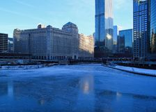 View of a blue and frigid winter morning in Chicago with reflections on a frozen Chicago River. View of a blue and frigid winter morning in Chicago with stock photo