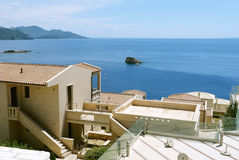 A view of the blue Ionian Sea, the mountains and stylish buildin Royalty Free Stock Photo