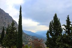 View of blue misty mountians and valley and twisting road framed by cedar and popular trees from ruins at Delphi Greece stock image