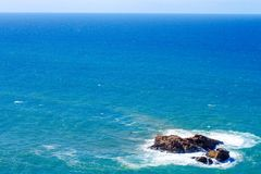 A view of the blue ocean from the top and only a small rocky island. On which the waves beat Stock Image