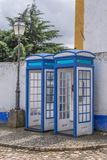 View of blue retro telephone booths, in street of the medieval village of Obidos stock photos