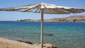View of the blue sea and beach umbrella stock footage