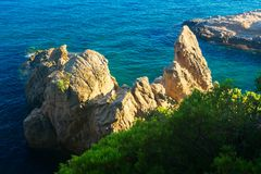 View on blue sea with rocky cliff in water in Lloret de Mar, Costa Brava, Spain. Scenic seascape of mediterranean royalty free stock images