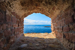 View of blue sea seascape from hole window frame in old stone wall. View of blue sea and sky from hole in old stonewall wall. Seascape in stone window casing Royalty Free Stock Photos