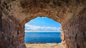 View of blue sea seascape from hole window frame in old stone wall Stock Image