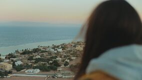 View of blue sea and small village from back of woman. Girl stay on top of the mountain and looking Into Horizon, 4k
