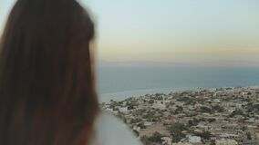 View of blue sea and small village from back of woman. Girl stay on top of the mountain and looking Into Horizon, full