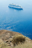 View of the blue sea and the white ship with the high coast of t. He island of Santorini, Greece Royalty Free Stock Photos