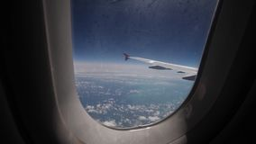 View of the blue sky and clouds through the window of the aircraft, Close up Airplane window with airplane wing. Traveling concept stock video