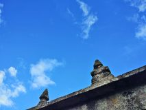 View of the blue sky from an old Galician granite stone wall crowned by pinnacles stock image