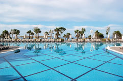 View of blue swimming pool, sunbeds and palm trees near the beac Royalty Free Stock Photography