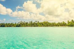 View of blue turquoise lagoon and far line of palm trees on tran Stock Photo