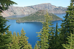 Blue water of Crater Lake between the trees Stock Image