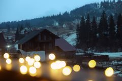 View of blurred Christmas lights and cottages near forest. In winter evening royalty free stock image